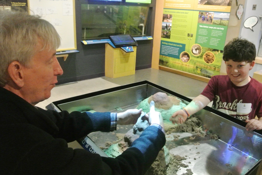 King Street mentor James Wolvington explores a soil erosion exhibit with his mentee Jasper at the ECHO Lake Aquarium and Science Center.